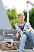 Young student sitting on university steps laptop — Stock Photo