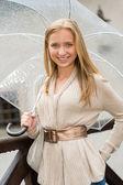 Gelukkig jongedame in regen met paraplu — Stockfoto