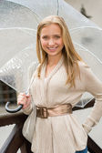 Young happy woman in rain with umbrella — Stok fotoğraf