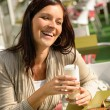 Woman at cafe bar holding latte drink — Stock Photo