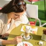 Woman eating cheesecake at cafe bar happy — Stock Photo