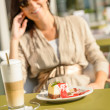 Cheesecake and latte cafe terrace woman sitting — Stock Photo