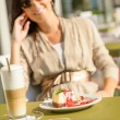 Cheesecake and latte cafe terrace woman sitting — Stock Photo #12729061