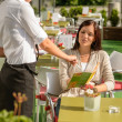 Waitress pointing menu woman in cafe bar - Stock Photo