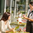 Waitress taking woman's order at cafe bar - Stock Photo