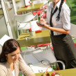 Stock Photo: Waitress waiting for woman to order menu