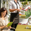 Stock Photo: Woman checking menu waitress bringing order coffee