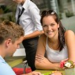 Stock Photo: Couple at cafe man looking at menu