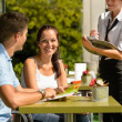 Couple at cafe ordering from menu waitress — Stock Photo #12729195