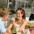 Woman feeding man cheesecake at cafe couple - Stock Photo