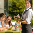 Waitress waiting for clients to decide order — Stock Photo #12729204