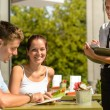 Couple at cafe ordering from menu waitress — Stok fotoğraf #12729206