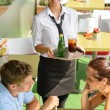Stock Photo: Waitress bringing beverages on tray to couple