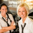 Cafe waitresses behind bar smiling at work — Stock Photo