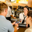 Man paying with credit card at cafe - Stock Photo