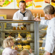 Foto Stock: Grandchildren asking grandmother for cakes at cafe