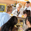 Buying cakes at cafeteria queue desserts - Stock Photo