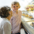 Woman with child girl choose cake bakery - Foto Stock