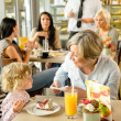 Child with grandmother at cafe eating cake — Stock Photo