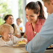 Mother and father with child eating cake - Stock Photo
