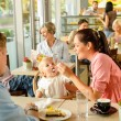 Father and mother feeding child cake cafe — Stock Photo #12729306