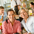 Mother and daughter relaxing in a cafe - Stock Photo