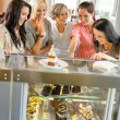 Group of friends looking at cakes cafe — Stock Photo