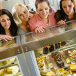 Women friends looking at cakes in cafe — Stock Photo #12729336