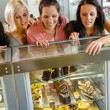 Stock Photo: Women friends looking at cakes in cafe