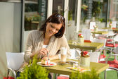 Woman at cafe eating cheesecake dessert happy — Stock Photo