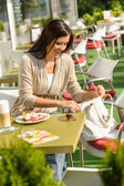 Woman looking in purse at cafe bar — Stock Photo