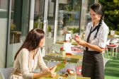 Waitress taking woman's order at cafe bar — Stock Photo