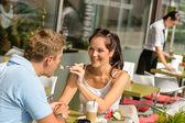 Woman feeding man cheesecake at cafe couple — Stock Photo