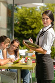 Waitress waiting for clients to decide order — Stock Photo