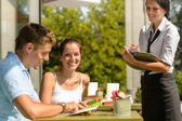 Couple at cafe ordering from menu waitress — Photo