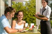 Couple au café ordonnant de serveuse menu — Photo