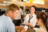 Couple paying bill at cafe cash desk — Stockfoto
