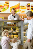 Grandchildren asking grandmother for cakes at cafe — Foto Stock
