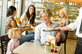 Mormor och barnbarn väntar tårta för café — Stockfoto