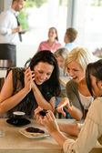 друзья, глядя на фотографии и смеясь кафе — Стоковое фото
