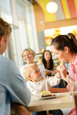 Father and mother feeding child cake cafe — Stock Photo