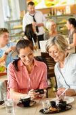 Mother and daughter looking at pictures cafe — Stock Photo