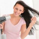 Smiling woman blow-drying long hair — Stock Photo