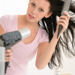 Woman blow-drying hair using round hairbrush — Stock Photo