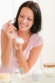 Smiling woman put moisturizer cream on nose — Stock Photo