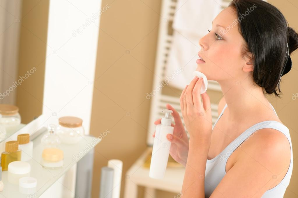 Young woman in bathroom clean face make-up removal looking mirror — Stock Photo #12816051