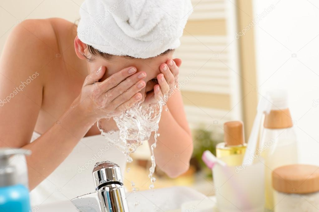 Woman splashing face with water above bathroom sink  Stock Photo #12816513