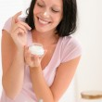 Smiling woman put moisturizer cream on nose — Stock Photo