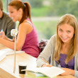 Student taking notes in study room - Stock Photo