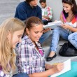 Stock Photo: Students sitting on school steps writing studying